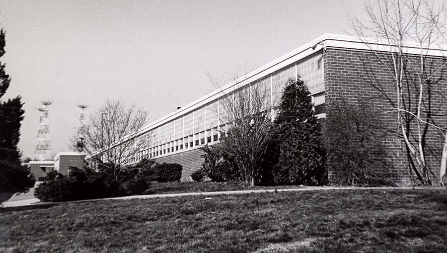 Black and white photograph of Haycock Elementary School taken circa 1968. The camera is on the eastern side of the building, looking down the front of the building toward the main entrance. Microwave towers are visible in the distance.