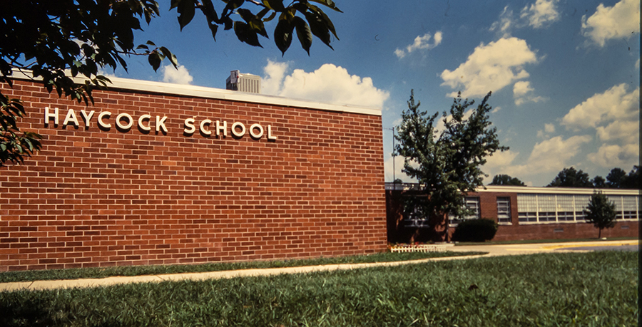 Color photograph of Haycock Elementary School from a 35 millimeter slide. Likely taken in the early 1980s. The front of the building is featured and the name Haycock School is visible on the brick wall.